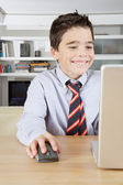 Young boy using a laptop computer at home to do his homework, smiling. — Stock Photo