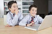 Two identical twin brothers sharing a laptop computer to do their homework — Stock Photo
