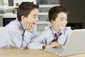 Two twin brothers sharing a laptop computer at home, laughing. — Stock Photo