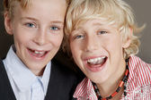 Close up portrait of two young brothers laughing with their heads together. — Stock Photo