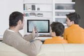 Pai com os irmãos gêmeos assistindo tv em casa, usando o controle remoto. — Foto Stock
