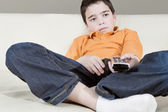 Young boy using a tv remote control while watching television sitting on a white leather sofa at home. — Foto de Stock