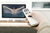 Man's hand holding a tv remote control, pressing a button while pointing at a flat screen tv. — Stock Photo