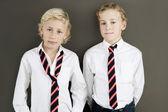 Twee school kinderen dragen van uniforme staande naast elkaar op een bruine achtergrond. — Stockfoto