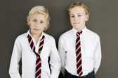 Two school kids wearing uniform standing next to each other on a brown background. — ストック写真