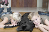 Two brothers at home relaxing on the floor their pet dog. — Stock Photo