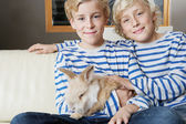 Two brothers and their rabbit pet sit together on a sofa at home, smiling. — Stock Photo