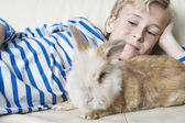 Young boy stroking his pet rabbit at home. — Stock fotografie