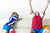 Two kids supporting different teams watching football and celebrating at home. — Stock Photo