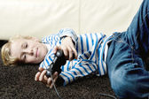 Young boy playing video games at home, laying down on the carpet. — Stock Photo