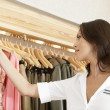 Store assistant sorting clothes on store's rails, close up. - Foto Stock