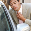 Attractive young businessman grooming using a car's reversing mirror to tidy his tie knot — Stock Photo #20077037