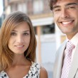 Portrait of a businessman and a businesswoman standing together in a classic office buildings street — Stock Photo