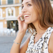 Profile view of an attractive businesswoman having a phone conversation in a classic city with traffic. — Stock Photo
