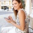 Young professional woman using a smart phone and electronic pen in a classic city, smiling. — Stock Photo