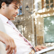 Stock Photo: Young professional man using a laptop pc while sitting on a wooden bench in a classic city square.