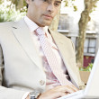 Close up portrait of a businessman sitting on a wooden bench using a laptop computer in the city. — Stock Photo