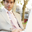 Young professional man using a laptop pc while sitting on a wooden bench in a classic city square. — Stock Photo