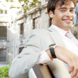 Portrait of a young attractive businessman sitting on a wooden bench in a classic city, smiling. — Stock Photo