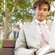 Young professional man using a laptop pc while sitting on a bench in a classic city square. — Stock Photo