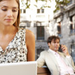 Businessman and businesswoman using technology while sitting on wooden benches in a classic city square. — Stock Photo