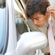 Attractive young businessman grooming using a car's reversing mirror to tidy his hair up. — Stock Photo #20077031