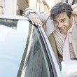 Young businessman grooming himself in the mirror of a parked car in the city. - Stock Photo