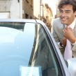 Attractive young businessman grooming using a car's reversing mirror to tidy his tie knot — Stock Photo