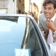 Stock Photo: Attractive young businessmgrooming using car's reversing mirror to tidy his tie knot