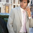 Businessman using a cell phone to make a phone call while standing by a car in the city. — Stock Photo #20077069