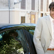 Businessman using a cell phone to make a phone call while standing by a car in the city. — Stock Photo