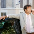 Businessman using a cell phone to make a phone call while standing by a car in the city. — Stock Photo #20077081