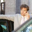 Businessman using a cell phone to make a phone call while standing by some cars in the city. — Stock Photo #20077091