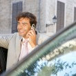 Foto de Stock  : Businessmusing cell phone to make phone call while standing some cars in city.