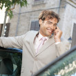 Businessman using a cell phone to make a phone call while standing some cars in the city. — Stock Photo