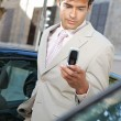 Businessman using a cell phone to send a message while standing by some cars in the city. — Stock Photo