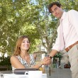 Stock Photo: Businessmand businesswomshaking hands while having coffee in terrace outdoors.