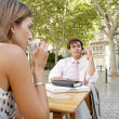 Business having a coffee while sitting at a coffee shop table in a town square. — Stock Photo #20077371