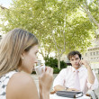Two business having a meeting in an outdoors cafeteria in the city and making a phone call. — Stock Photo