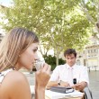 Businessman and businesswoman using technology while at a coffee shop terrace table outdoors in a classic city. — Stock Photo #20077385