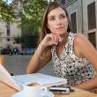 Businesswoman using a laptop computer and other technology while sitting down at a coffee shop terrace table — Stock Photo #20077445
