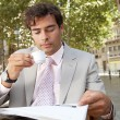 Stock Photo: Businessman reading the newspaper while drinking coffee in a coffee shop terrace