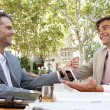 Two businessmen having a meeting in a coffee shop terrace outdoors. — Stock Photo #20077649