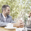Two businessmen having a meeting in a coffe shop's terrace in the city, outdoors. — Stock Photo