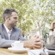 Stock Photo: Two businessmen having meeting in coffe shop's terrace in city, outdoors.