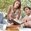 Three business having a meeting while sitting at a coffee shop terrace outdoors. — Foto de Stock