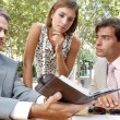 Three business having a meeting while sitting at a coffee shop terrace outdoors. — Stock Photo