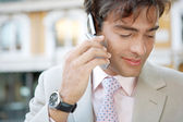 Portrait of an attractive young businessman having a cell phone conversation outdoors in the city. — Stock Photo