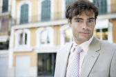 Portrait of a young businessman in a European city background. — Stock Photo