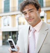 Young attractive businessman in a European city with classic office buildings in the background — Stock Photo
